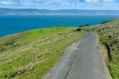 El camino pavimentado lleva al océano azul Imagen de archivo