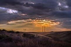 El camino que desaparece al horizonte debajo del sol irradia venir abajo canal las nubes tempestuosas dramáticas Puesta del sol e Imagen de archivo