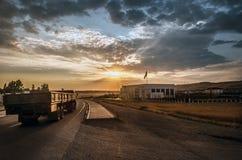 El camino que desaparece al horizonte debajo del sol irradia venir abajo canal las nubes tempestuosas dramáticas Puesta del sol e Imagen de archivo libre de regalías