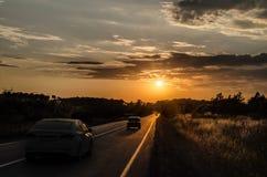 El camino que desaparece al horizonte debajo del sol irradia venir abajo canal las nubes tempestuosas dramáticas Puesta del sol e Imagenes de archivo