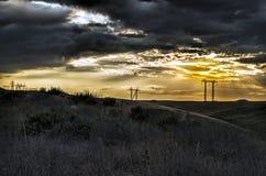 El camino que desaparece al horizonte debajo del sol irradia venir abajo canal las nubes tempestuosas dramáticas Puesta del sol e Fotos de archivo libres de regalías