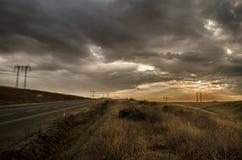 El camino que desaparece al horizonte debajo del sol irradia venir abajo canal las nubes tempestuosas dramáticas Puesta del sol e Fotografía de archivo libre de regalías