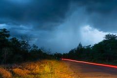 El camino que eso lleva a la lluvia el caer de la nube gruesa fotografía de archivo libre de regalías