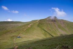 El camino que lleva abajo de la cumbre de Cribyn hasta la cumbre de la fan de la pluma y en el Brecon baliza el parque nacional Foto de archivo