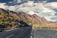 El camino que retrocede en la distancia, lleva a las atracciones principales del volcán de Tenerife - de Teide Foto de archivo