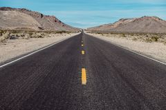 El camino recto largo escénico vacío del desierto con la marca amarilla alinea Imágenes de archivo libres de regalías