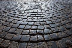 El camino viejo se pavimenta con los adoquines de piedra Imágenes de archivo libres de regalías