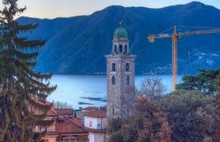 El campanario y el lago Lugano Imagen de archivo libre de regalías