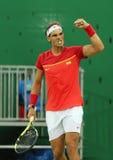 El campeón olímpico Rafael Nadal de España celebra la victoria después de que los hombres escojan el partido de la Río 2016 Juego Imagenes de archivo