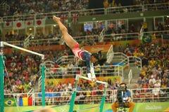 El campeón olímpico Simone Biles de Estados Unidos compite en las barras desiguales en la gimnasia versátil del equipo de mujeres Fotografía de archivo