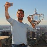 El campeón Stanislas Wawrinka del Grand Slam de tres veces de Suiza toma el selfie con el trofeo del US Open en el top de la roca Foto de archivo libre de regalías