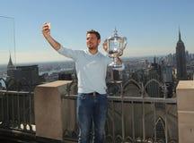 El campeón Stanislas Wawrinka del Grand Slam de tres veces de Suiza toma el selfie con el trofeo del US Open en el top de la roca Imagen de archivo