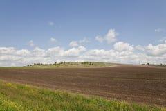 El campo arado en una cuesta de una colina inferior Foto de archivo libre de regalías
