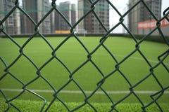 El campo de fútbol en el tejado rodeado por los edificios Fotografía de archivo libre de regalías