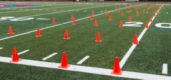 El campo del césped puso con los conos anaranjados para los ejercicios de la agilidad Fotografía de archivo