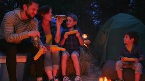 El campo, los padres jovenes con los niños come maíz y la cerveza de consumición en el día de fiesta en camping, consumición feli almacen de video