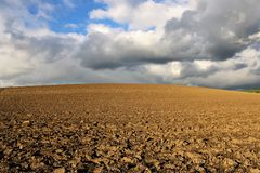 El campo vacío se preparó para el invierno con las nubes mezcladas fotos de archivo libres de regalías