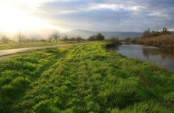 El campo y el río verdes se encendieron por la luz fuerte de Sun Fotos de archivo libres de regalías