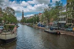 El canal arbolado con los edificios de ladrillo viejos, aguja, amarró los barcos y el cielo azul soleado en Amsterdam Imagen de archivo libre de regalías