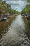 El canal arbolado con los edificios de ladrillo viejos, puente, amarró los barcos y el cielo azul nublado en Amsterdam Fotos de archivo libres de regalías