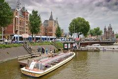 El canal del barco cruza en un río con la estación central de Amsterdam en el fondo con el cielo nublado Fotos de archivo libres de regalías