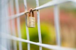 El candado cerrado se cerró sobre la cerca cuadrada con el focu bajo de Exteme fotos de archivo libres de regalías