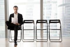 El candidato de trabajo lee el curriculum vitae mientras que espera entrevista Fotos de archivo libres de regalías