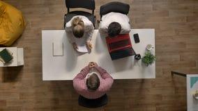 El candidato masculino a trabajo es entrevistado con por dos patrones, topshot, sentándose en oficina moderna almacen de video