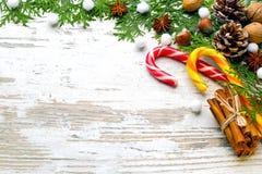 El canela, caramelo un gancho, nueces, un anisetree, abeto ramifica, nieve en un cierre de madera ligero del fondo para arriba Imagenes de archivo