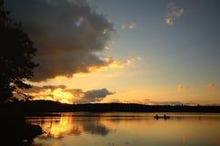 El Canoeing en la puesta del sol en un lago wilderness Imagen de archivo libre de regalías