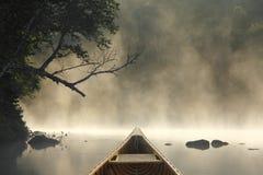 El Canoeing en un lago brumoso Fotografía de archivo