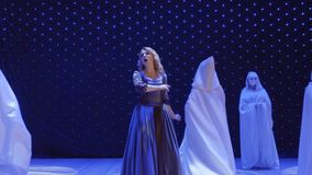 El cantante hermoso baila con el extranjero en capa en etapa en teatro metrajes