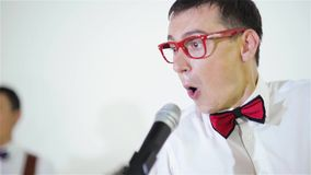 El cantante joven divertido canta una canción en un micrófono, primer