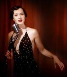 El cantante retro canta sostener el micrófono del vintage Foto de archivo libre de regalías