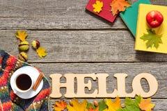 El capítulo de las hojas rojas, verdes y amarillas del otoño, manzanas con la taza de café o té, palabra grande hola reserva en v imágenes de archivo libres de regalías