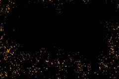 El capítulo de las partículas de oro de las burbujas de la chispa del brillo protagoniza en el fondo negro, día de fiesta festivo imagen de archivo