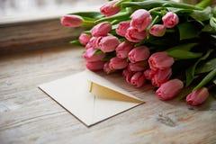El capítulo de tulipanes frescos arregló en fondo de madera con el papel Imagenes de archivo