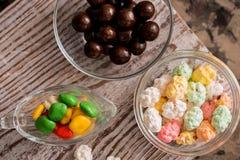 El capítulo del caramelo clasificado brillante colorido en cuencos y los tarros, los bastones de caramelo y arco iris coloreó las Foto de archivo libre de regalías