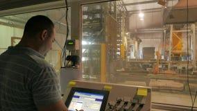 El capataz controla la producción del cuarto del operador en una fábrica de los bloques de cemento metrajes