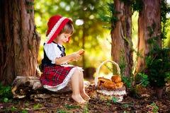 El Caperucita Rojo en el bosque se sienta en un registro con una cesta de empanadas imagen de archivo