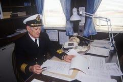 El capitán del transbordador Bluenose que hace el papeleo en su escritorio, Maine Fotografía de archivo