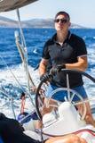 El capitán del hombre joven dirige el barco del yate de la navegación de la rueda Imagen de archivo