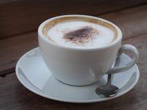 El capuchino caliente con la burbuja fina completa poner crema poco polvo de cacao sirvió en la taza de café de cerámica blanca foto de archivo