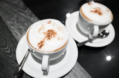 El capuchino, dos tazas de café con leche hace espuma Foto de archivo