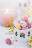 El caramelo de chocolate coloreó los huevos de Pascua en vela ardiente de la taza de cerámica, pequeñas flores Foto de archivo libre de regalías