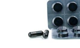 El carbón de leña activado hace tabletas píldoras en paquete de ampolla en el fondo blanco con el espacio de la copia para el tex Imagen de archivo