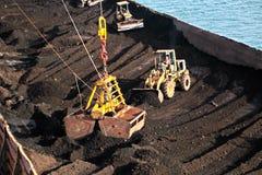 El carbón del cargamento del cargo barges sobre un carguero de graneles que usa las grúas y los ganchos agarradores de la nave en imagen de archivo libre de regalías