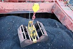 El carbón del cargamento del cargo barges sobre un carguero de graneles que usa las grúas y los ganchos agarradores de la nave en fotos de archivo libres de regalías