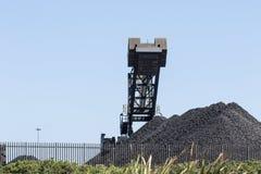 El carbón descarga con maquinaria en un fondo del cielo azul foto de archivo libre de regalías