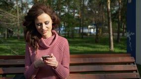 El cardán tiró de la muchacha adolescente femenina que hablaba en el teléfono que se sentaba en banco en el día soleado de la pri almacen de video